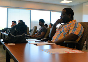 Fellow competitors watch intently as proposed applications are presented during the Hackathon.