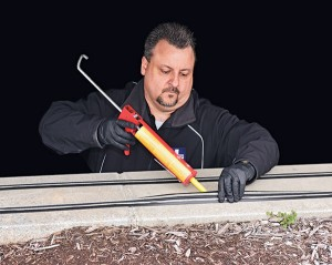 Tim Periard, Bird Doctor's VP of operations, uses adhesive to secure  an electrified track.