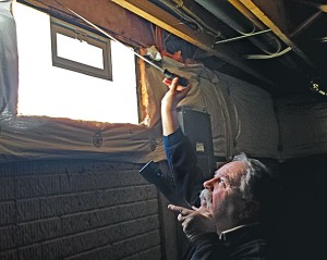Dave Daniels of Speed Exterminating uses a long metal poker to investigate for evidence of termites around basement insulation.  Photo: Will Nepper