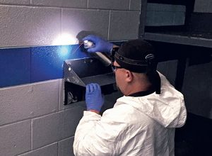Termitech's Steve Parke applies an aerosol in cracks and crevices in an  inmate cell.  Photo: Termitech