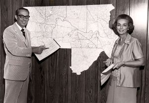 Jo and John Cook stand in front of a map showing their service area.  Photo: Cook's Pest Control