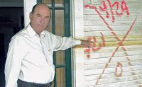 Martin points to a water line on a home, illustrating the devastation Hurricane Katrina caused.Photo: Courtesy of Joe Martin