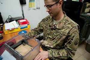 Argo holds a box containing a black fat-tailed scorpion and a keeled rock gecko Nov. 3 at an undisclosed location in Southwest Asia. (U.S. Air Force photo by Staff Sgt. William Banton)
