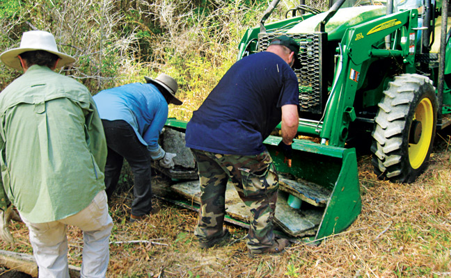 Team members lead debris onto the tractor