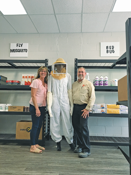 Office Manager Laura Lentz and Supervisor George Cochran stand with a Schopen Pest Solutions retail display. PHOTO: PETE SCHOPEN