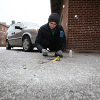 Student investigates the ground at a test crime scene in the snow. Photo: Tom Campbell