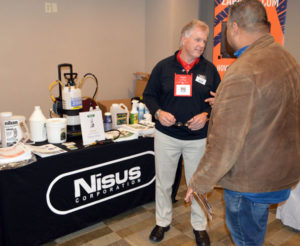 Harry Bryan, Area Sales Manager with Nisus Corp., talks with an attendee at the New York Pest Expo about Niban. PHOTO: MARTY WHITFORD