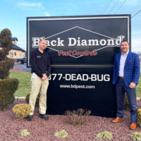 From left, New Elizabethtown Branch Manager Eric Freedland poses with Black Diamond Pest Control CEO Keith Duncan, Jr. in front of the Black Diamond sign. PHOTO: BLACK DIAMOND PEST CONTROL
