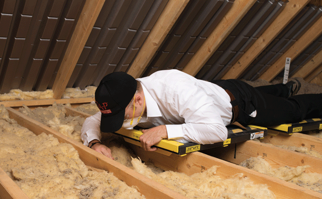 A PMP inspects the condition of existing attic insulation. PHOTO: PEST CONTROL INSULATION