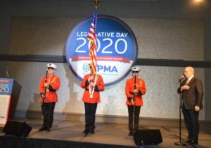 """A color guard stands by as Rose Pest Solutions' Russ Ives sings """"The Star-Spangled Banner"""" before lunch is served. PHOTO: PMP STAFF"""