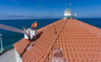 Learn the ins and outs of lift safety before taking on a big job like this, installing bird repellent dishes on the roof tiles of a pier structure. PHOTO: BIRD BARRIER