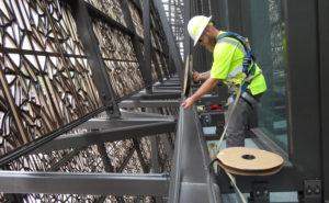 Blue Ridge Wildlife & Pest Management Technician Jason Davis installs Bird-Shock Flex-Track on the roof of the National Museum of African American History & Culture. PHOTO: BLUE RIDGE WILDLIFE & PEST MANAGEMENT
