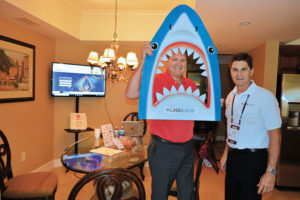 """Chip Hughes, right, co-owns LabelSDS.com with his wife, Debbie. The pair went all in on branding their meeting room suite with a """"Be a Business Shark"""" theme, replete with Debbie's delicious """"shark bait"""" snack mix, shark beverage cozies and the sharkhead cutout that the game Jerry Smith, Dial Pest Control, is pictured using. PHOTO: PMP STAFF"""
