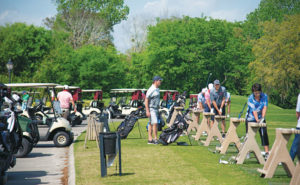 Golfers get in a few practice swings before the event. PHOTO: LOU FERRARO, PARK SOUTH PHOTOGRAPHY