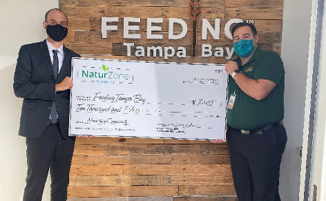 Managing Partner Andrew Longfellow presenting a $10,000 check to Feeding Tampa Bay. IMAGE: NATURZONE