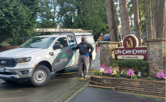 Gil Flores, a technician at Cascade Pest Control, stands in front of the residential care facility in Kirkland, Wash., where the COVID-19 pandemic first appeared in the U.S. PHOTO: ALEAH TREFTZ, CASCADE PEST CONTROL