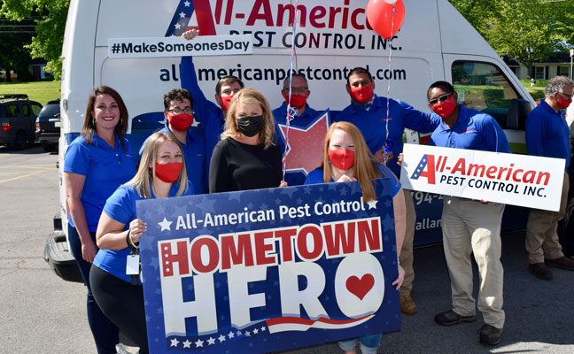 Brandi Nunnery, in black mask, is surrounded by members of the All-American Pest Control team after the Hometown Hero award ceremony. PHOTO: ALL-AMERICAN PEST CONTROL