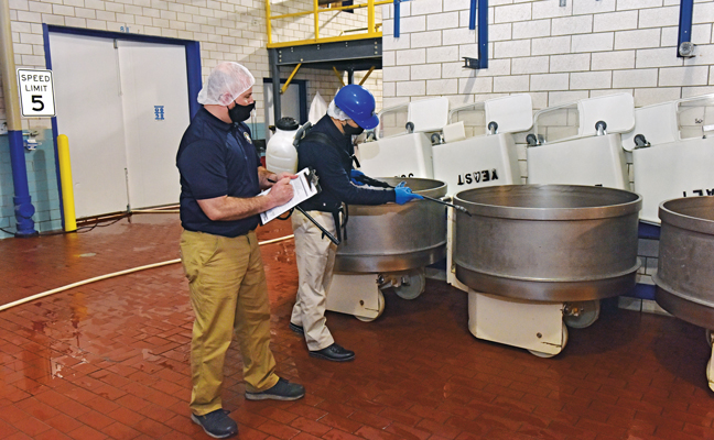 RK Environmental Services (RKE) Regional Operations Manager Chris Lazo, left, fills out a report as RKE Virucidal Program Service Specialist Johnny Echeverria begins to disinfect commercial mixing equipment at an account. PHOTO: FRED MILLER PHOTOGRAPHY