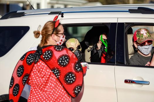 """Horizon Pest Solutions Owner Melisa Arnold, ACE, passes out Halloween candy in a """"Trick or Treat Drive Thru"""" event she helped organize. PHOTO: HORIZON PEST CONTROL"""